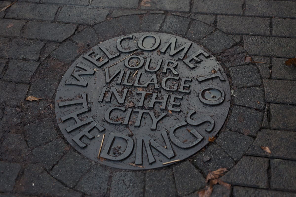 "A plaque on the floor reads ""welcome to the Dings, our village in the city"""