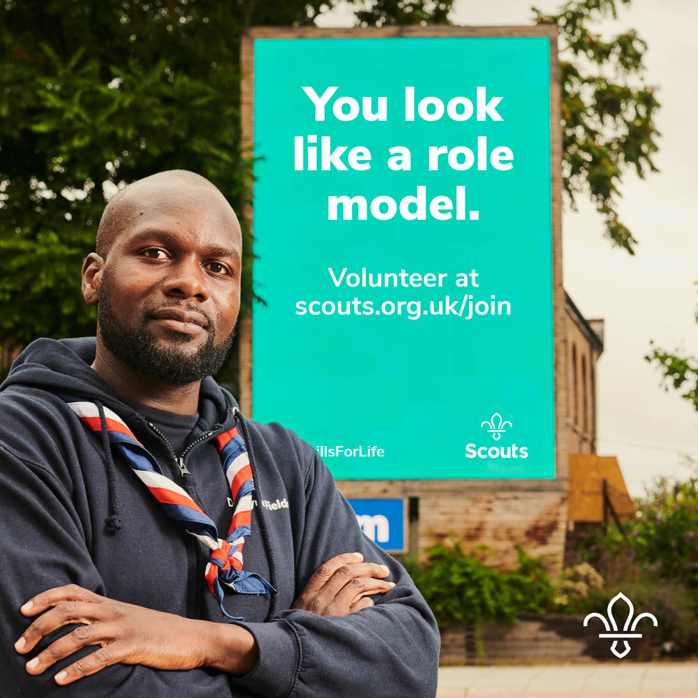 """Dwayne Fields standing in front of a Scout banner that says """"You look like a role model.'"""