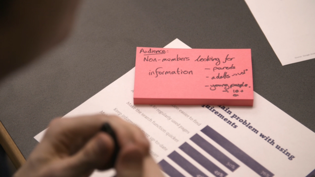Post it note block on a sheet of paper with a bar graph - image is blurred. Hands in the foreground.